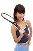 Young woman with tennis racket, smiling at camera - Asia Images Group