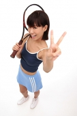 Young woman with tennis racket, looking up at camera, making hand sign - Asia Images Group