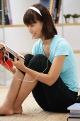 Young woman looking through magazine, wearing earphones - Asia Images Group