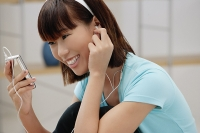 Young woman listening to MP3 player - Asia Images Group