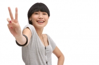 Young woman smiling at camera, making peace sign - Asia Images Group