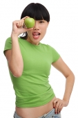 Young woman in green T-shirt, holding green apple - Asia Images Group