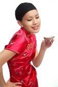 Young woman in cheongsam holding Chinese teacup - Asia Images Group