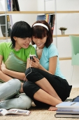 Young women wearing earphones, listening to MP3 player - Asia Images Group