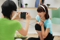 Young woman taking a picture of another young woman - Asia Images Group