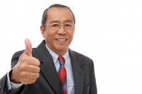 Businessman looking at camera, making thumbs up sign - Asia Images Group