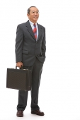 Businessman standing with briefcase - Asia Images Group