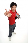 Young man with motorcycle helmet, making peace sign - Asia Images Group