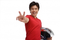 Young man carrying helmet, making peace sign - Asia Images Group