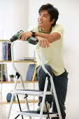 Man leaning on stepladder, holding drill - Asia Images Group