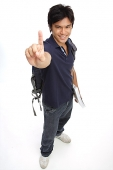 Young man carrying books and a backpack, making hand sign - Asia Images Group