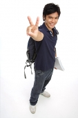 Young man carrying books and a backpack, making peace sign - Asia Images Group