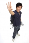 Young man with books and a backpack, making hand sign - Asia Images Group