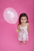 Girl holding balloon, looking up at camera - Asia Images Group