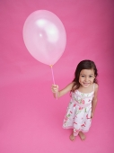 Girl with balloon, smiling at camera - Asia Images Group