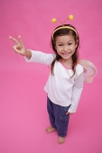 Young girl wearing fairy wings and deely bopper, making peace sign - Asia Images Group