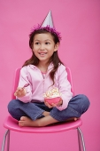 Girl with party hat, sitting on chair, holding bowl of cake - Asia Images Group