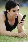Man lying on grass, using mobile phone - Asia Images Group