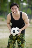 Man holding soccer ball, smiling at camera - Asia Images Group