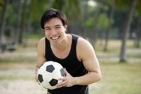 Man holding soccer ball, smiling - Asia Images Group