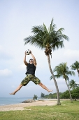 Man jumping in air to catch soccer ball - Asia Images Group