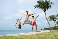 Three men jumping in air, arms outstretched - Asia Images Group