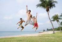 Three men jumping in air, looking at camera - Asia Images Group