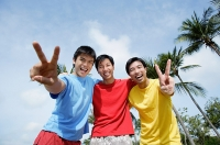 Men with arms around each other, looking at camera, making peace sign - Asia Images Group