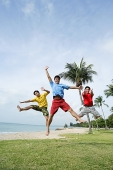 Three men  on beach, jumping in air, looking at camera - Asia Images Group