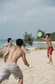 Three men on beach playing with Frisbee - Asia Images Group