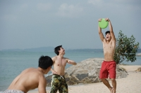 Men on beach playing with Frisbee - Asia Images Group