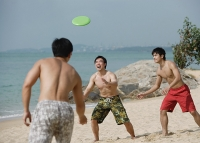 Three young men on beach playing with Frisbee - Asia Images Group