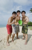 Three men on beach, standing side by side, making hand sign - Asia Images Group