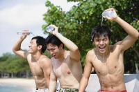 Three men sitting side by side, pouring water on themselves - Asia Images Group