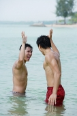 Two men standing in sea, giving high fives - Asia Images Group