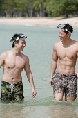 Two men wading in sea, wearing goggles - Asia Images Group