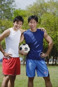 Two men standing together, one holding soccer ball - Asia Images Group