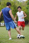 Two men in park, playing soccer - Asia Images Group