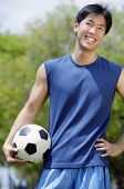 Man holding soccer ball, looking at camera - Asia Images Group