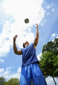 Man looking up at soccer ball - Asia Images Group