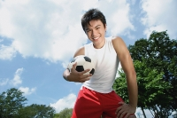 Young man holding soccer ball, smiling at camera - Asia Images Group