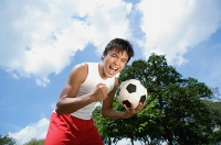Young man with soccer ball, looking at camera, hand in a fist - Asia Images Group
