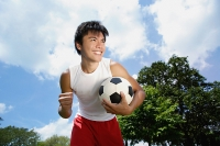 Young man with soccer ball, hand in a fist, smiling - Asia Images Group