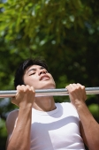 Young man using chin-up bar - Asia Images Group