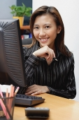 Female executive at desk, hand on chin, smiling at camera - Asia Images Group