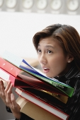 Female executive carrying folders and binders - Asia Images Group