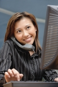 Female executive at desk, using computer and telephone, smiling - Asia Images Group