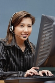 Female executive with hands free device, using computer - Asia Images Group