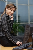 Businesswoman sitting on desk, using telephone - Asia Images Group