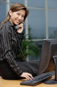 Businesswoman sitting on desk, using telephone, smiling at camera - Asia Images Group